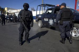 Mexican federal police officers stand in the middle of a street during a search operation after gunmen opened fire on two men at a stop sign in Ciudad Juarez, Mexico, Friday, Dec. 10, 2010.