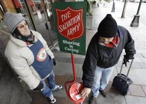 Donald Baca, right, drops money into a Salvation Army red kettle as bell ringer Mark Pearson looks on in downtown Seattle Wednesday, Dec. 17, 2008.