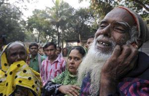 A Bangladeshi man, right, reacts as he looks for his son's body outside a garment factory where a fire killed more than 110 people Saturday near Dhaka, Bangladesh, Monday, Nov. 26, 2012.
