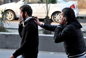 A Syrian helps a man who was injured after two cars bombs exploded, at Jaramana neighborhood, in the suburb of Damascus, Syria, Wednesday, Nov. 28, 2012.