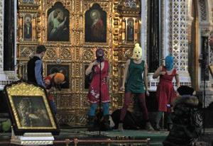 In this Feb. 21, 2012 photo, members of the Russian radical feminist group Pussy Riot try to perform at the Christ the Saviour Cathedral in Moscow.