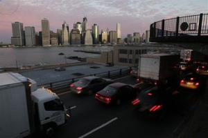 Early morning traffic in Brooklyn moves slowly beneath the Manhattan skyline, Thursday, Nov. 1, 2012 in New York.
