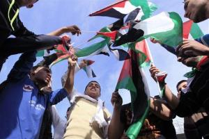 Palestinian refugees wave Palestinian flags during a rally in front the United Nations building in Beirut, Lebanon, Thursday.