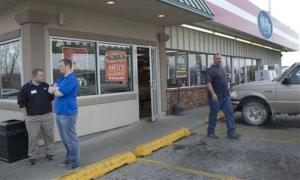 A customer walks out of the Trex Mart convenience store, right, while manager Chris Nauerz, left, and son of the owner Baron Hartell stand outside, in Dearborn, Mo., Thursday, Nov. 29, 2012.