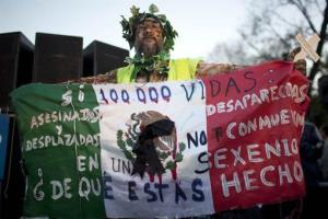 A man holds Mexico's flag during a protest against violence in Mexico City, Wednesday, Nov. 28, 2012.