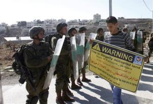 A Palestinian protester holds a placard in front of Israeli soldiers during a demonstration in the West Bank village of al-Masara, near Bethlehem, on Friday.