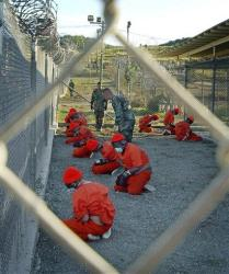 In this Jan. 11, 2002, file photo, detainees sit in a holding area at the Guantanamo Bay U.S. Naval Base in Cuba.