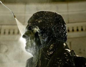 In this file photo, a National Park Service worker uses a pressurized sprayer to wash down the five-ton bronze statue of Thomas Jefferson at the Jefferson Memorial.