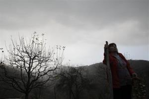 In this Nov. 30, 2012, photo Milka  Prokic is seen at twilight with a garland of garlic and a wooden stake, in the village of Zarozje, near the Serbian town of Bajina Basta.