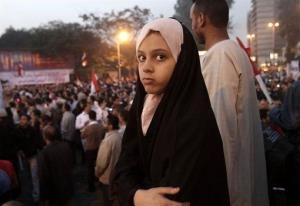 An Egyptian girl watches supporters of President Mohammed Morsi during a rally in front of Cairo University, Egypt, Saturday, Dec. 1, 2012.