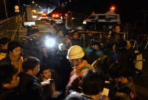 A worker speaks to reporters near the Sasago Tunnel where a collapse took place in Koshu, Yamanashi Prefecture, Japan, Sunday, Dec. 2, 2012.