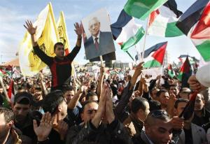 Palestinians wave flags and pictures of Mahmoud Abbas as they celebrate their successful bid to win UN statehood recognition in Ramallah, Sunday, Dec. 2, 2012.