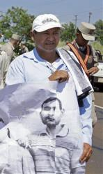 Vidal Vega, left, holds a banner during a march in Paraguay earlier this month.