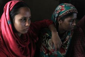 In this photo taken on Friday Nov. 29, 2012, Roksana, 20, left, a survivor of a garment factory fire, sits in her house in Dhaka, Bangladesh.