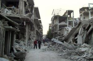 Syrian citizens walk in a destroyed street in Homs that was attacked by the regime's aircraft last week.