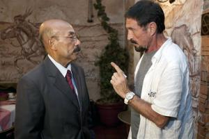 Software company founder John McAfee talks to his lawyer Telesforo Guerra, right, after giving an interview at a local restaurant in Guatemala City, Tuesday, Dec. 4, 2012.