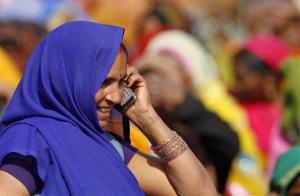 An Indian woman talks on her mobile phone at an election rally in this file photo.