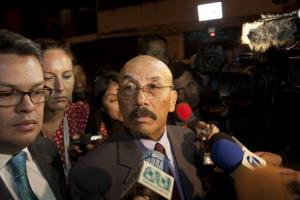 John McAfee's lawyer Telesforo Guerra, center, speaks to journalists Wednesday, Dec. 5, 2012, in Guatemala City.