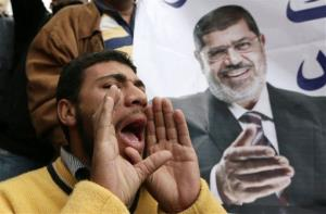 A supporter of Egyptian President Mohamed Morsi, pictured at right, chants slogans during a demonstration outside the presidential palace, in Cairo, Egypt, Wednesday, Dec. 5, 2012.