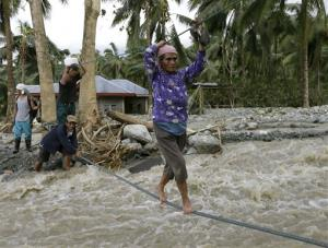 Residents cross a river using suspended ropes at Andap, New Bataan township, Compostela Valley in southern Philippines Wednesday, Dec. 5, 2012.