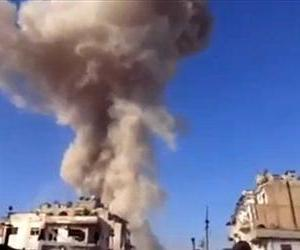 In this image taken from video, smoke rises from a building after a warplane attack in Homs, Syria, Nov. 28, 2012.