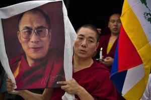 An Tibetan Buddhist monk carries a portrait of the Dalai Lama as he participates in a candlelit vigil in Dharmsala, India, in June.