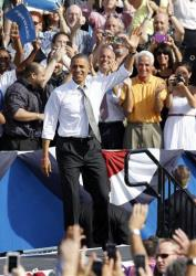 President Obama, accompanied by former Florida Gov. Charlie Crist, second from right, waves to supporters as he arrives at a campaign stop in Delray Beach, Fla., Tuesday, Oct. 23, 2012.
