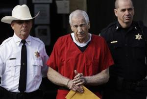 In this Oct. 9, 2012 file photo, former Penn State University assistant football coach Jerry Sandusky, center, is taken from the Centre County Courthouse after being sentenced in Bellefonte, Pa.