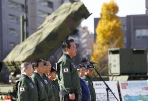 Japanese Prime Minister Yoshihiko Noda, center, stands by a ground-based Patriot Advanced Capability-3 interceptor during his inspection tour to the Defense Ministry in Tokyo, Friday, Dec. 7, 2012.