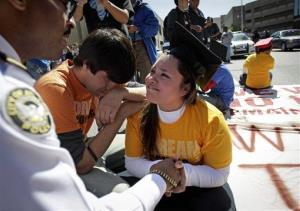 In this April 5, 2011 file photo, illegal immigrant Viridiana Martinez, right, is comforted by an activist as an Atlanta policeman warns her of arrest unless she moves while protesting.