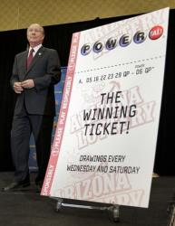 Arizona Lottery Executive Director Jeff Hatch-Miller stands next to an enlargement of the winning $587.5 Million Powerball ticket, Friday, Dec. 7, 2012 in Scottsdale, Ariz.