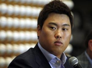 In this Nov. 15, 2012, file photo, pitcher Ryu Hyun-jin, of South Korea, pauses during a baseball news conference in Newport Beach, Calif.