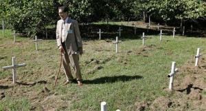 In this Oct. 21, 2008 file photo, Dick Colon, a member of the White House Boys, walks through  grave sites near the Arthur G. Dozier School for Boys  in Marianna, Fla.