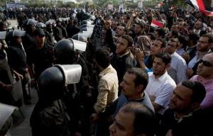 Supporters of Egyptian President Mohammed Morsi chant slogans as riot police stand guard in front of the entrance of Egypt's top court.