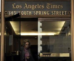 In this Dec. 8, 2008 file photo, an unidentified woman leaves the Los Angeles Times building in downtown Los Angeles.