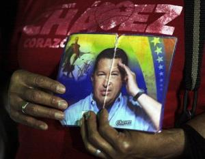 A person holds up images of Venezuela's President Hugo.