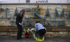Leslie King, right and Tenille Beseda place flowers Wednesday at the entrance of Clackamas Town Center Mall in Clackamas, Ore.