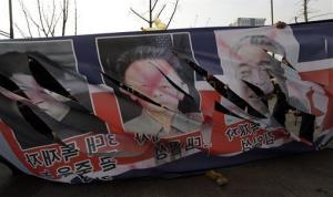 South Korean protesters tear pictures of Kim Jong Un, Kim Jong Il, and Kim Il Sung, the late founder of North Korea, during a rally denouncing the rocket launch, Thursday, Dec. 13, 2012.