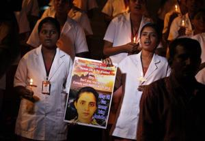 Students of a nursing college pray as they participate in a candle light vigil organized by a local politician in Bangalore, India, Thursday, Dec. 13, 2012, to condole the death of Jacintha Saldanha, a nurse at King Edward VII hospital in London, who killed herself after taking a hoax call...