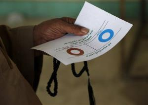 An Egyptian man holds a ballot before casting his vote in Cairo.