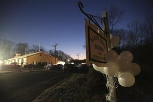 White balloons decorate a sign for the Sandy Hook Elementary School Saturday morning.