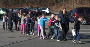 Connecticut State Police lead a line of children from the Sandy Hook Elementary School in Newtown, Conn. on Friday, Dec. 14, 2012, after a shooting at the school.