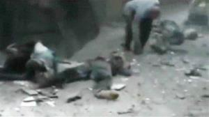 In this file photo from Friday, Aug. 3, 2012, bodies lie in the street after mortars rained down on a crowded marketplace in the Yarmouk refugee camp in Damascus, Syria.