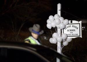 White balloons decorate the sign for the Sandy Hook Elementary School as a Connecticut State Trooper stands guard.