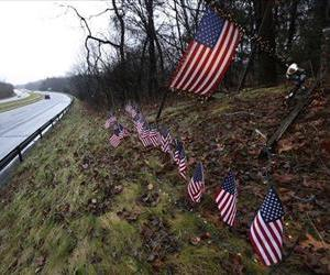 Twenty-seven small US flags adorn a large flag on a makeshift memorial on the side of Highway 84 near the Newtown, Conn.