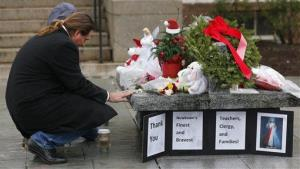 A couple pause at a memorial outside town hall in Newtown, Conn., Monday, Dec. 17, 2012.