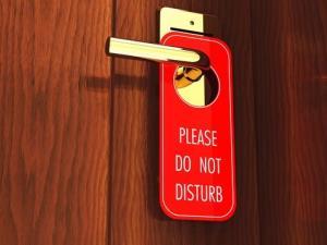 A Do Not Disturb sign hangs on a hotel room door.
