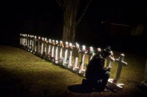 Frank Kulick adjusts a display of wooden crosses and a Jewish Star of David, representing the victims of the Sandy Hook Elementary School shooting, on his front lawn, Dec. 17, 2012, in Newtown, Conn.