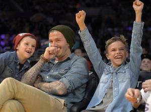 David Beckham laughs with his sons Romeo, right, and Cruz, left, as they watch a basketball game between the Los Angeles Lakers and Phoenix Suns, in this photo dated Nov. 16, 2012, in Los Angeles.