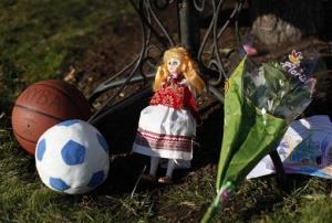 A basketball, soccer ball, doll, flowers, and a child's drawing sit at a memorial for shooting victims outside Saint Rose of Lima Roman Catholic Church in Newtown, Conn.